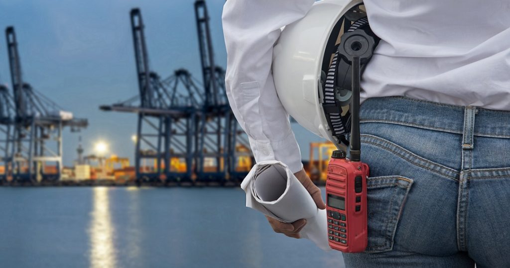 Engineer woman holding white helmet and blueprint with radio for workers security control at Container Cargo freight ship for Logistic Import Export background. Engineer Concept