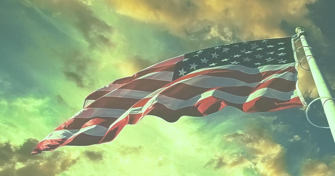 american flag waving blue sky