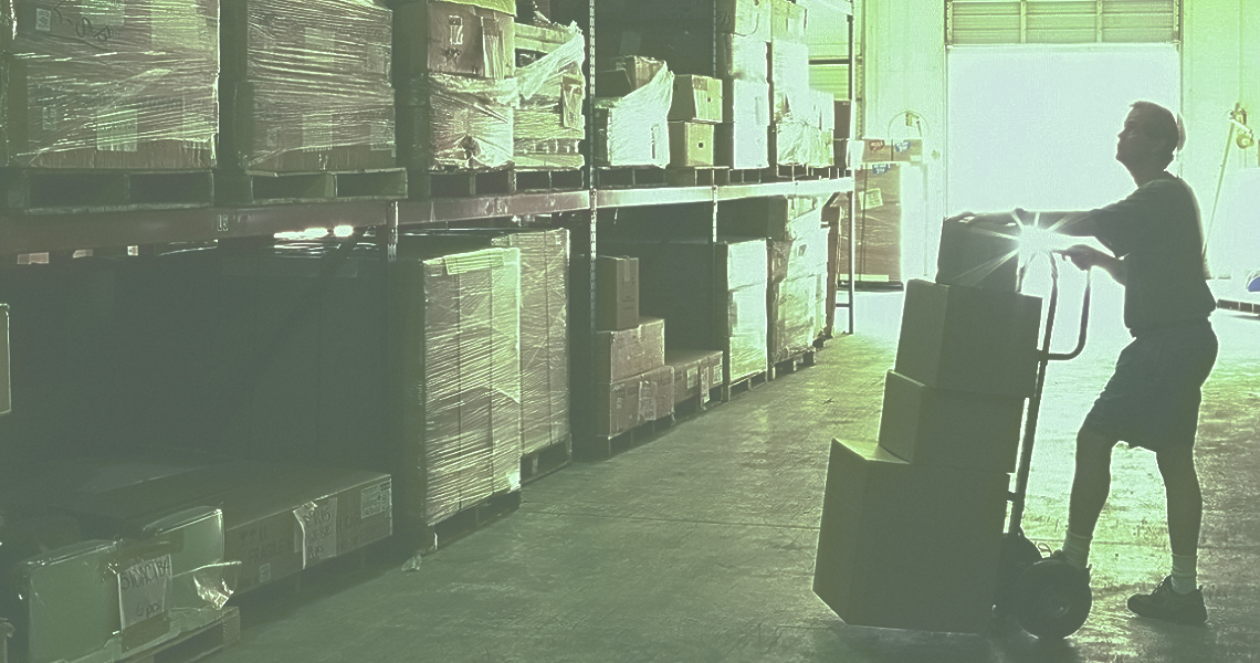 A warehouse worker moving a shipment of boxes using a hand truck.