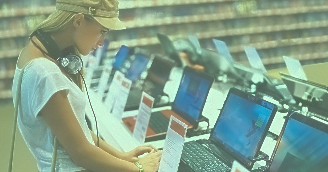 Pretty young woman checking the latest laptop computer in an electronic store